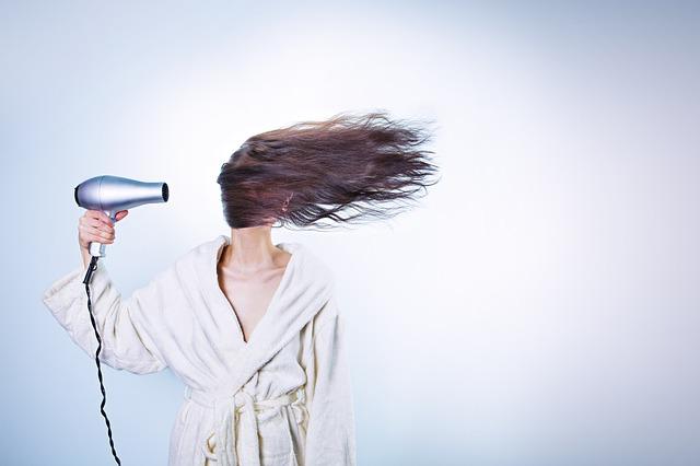 kobieta suszy włosy